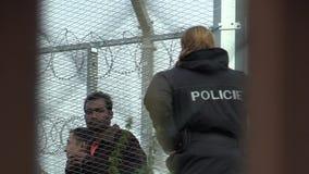 VYSNI LHOTY, ЧЕХИЯ, 18-ОЕ ОКТЯБРЯ 2015: Беженец, переселенцевое размещение в лагере военнопленных в Vysni Lhoty, полиции сток-видео