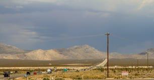 Wüstengebiet mit Stromleitung und Straße stockfotografie