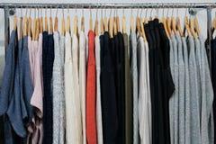 Wählen der modernen Kleidung der verschiedenen Farben auf hölzernen Aufhängern Hintergrund für das Konzepteinkaufen und -rabatte lizenzfreie stockfotos