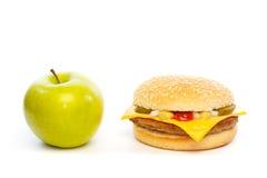 Wählen Sie: Apfel oder Cheeseburger Stockfoto