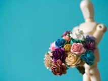 Wählen Sie Fokus der Blume vor Die hölzerne Marionette hält Blume und Stellung auf der hölzernen Tabelle Lizenzfreies Stockfoto