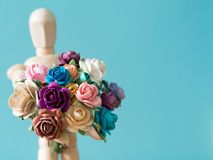 Wählen Sie Fokus der Blume vor Die hölzerne Marionette hält Blume und Stellung auf der hölzernen Tabelle der Hintergrund ist blau Stockfotografie