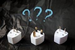 Wählen von den verschiedenen Adaptern des elektrischen Steckers Schwierigkeiten und Probleme des Reisens Lizenzfreies Stockfoto