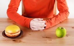 Wählen zwischen Donut und Apfel Stockfotografie
