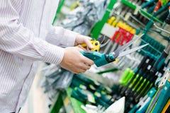 Wählende und kaufende Scheren für Beschneidungszutat-Baumgras in der Gartenwerkzeugabteilung auf dem DIY-Einkaufsspeicher Lizenzfreie Stockfotografie