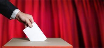 Wähler hält Umschlag in der Hand über Abstimmungs-Stimmzettel auf rotem Hintergrund Freiheits-Demokratie-Konzept lizenzfreie stockfotografie