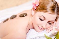 Während Badekurortverfahrensder steintherapiemassage mustert das blonde hübsche Mädchen, das Spaß hat, geschlossenes Bild Stockfotos