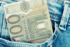 Währungseuro in den Jeans stecken ein Bargeld, das für den Einkauf zahlt lizenzfreie stockbilder