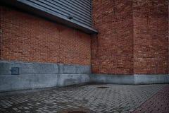 Wände des Gebäudes des roten Backsteins und des grauen Ziegelsteinbodens Lizenzfreie Stockfotografie