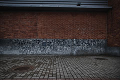 Wände des roten Backsteins und schroffer Ziegelsteinbodenhintergrund Stockfoto
