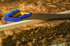 Wärmedämmungsrohbaumwolleschnitt mit einer Säge Stockfotos