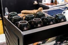 Wärmen Sie die umgedrehten Kaffeetassen, die auf Espressomaschine vorbereitet werden stockbilder