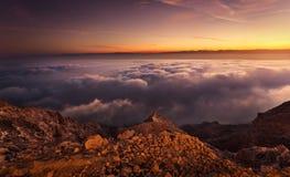 Wärmen Sie glühenden Sonnenaufgang über Hafeet-Berg über den Wolken stockfotografie