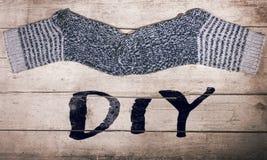 Wärmen Sie selbst gemachte Wollsocken auf Holztisch, das diy Wort Stockfotos