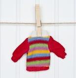 Wärmen Sie Winter Striped Strickjacke auf einer Wäscheleine Stockfoto