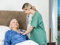 Wärter, der ältere Frau am Pflegeheim überprüft Lizenzfreies Stockfoto