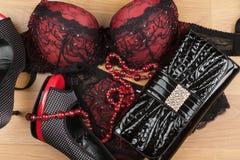 Wäsche, Perlen, Schuhe und Tasche, die auf dem Laminat liegen Lizenzfreie Stockbilder