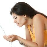 Wäschen des jungen Mädchens mit Trinkwasser Lizenzfreie Stockfotos