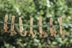 WÄSCHEREI-Wort geschrieben durch gehangene hölzerne Buchstaben auf Seil am Garten stockbilder