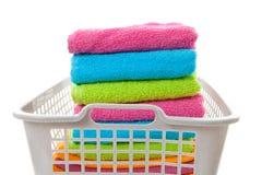Wäschereikorb gefüllt mit bunten gefalteten Tüchern Stockfotos
