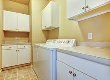 Wäschereiraum mit weißen Kabinetten und gelben Wänden. Lizenzfreie Stockfotos
