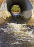Wässern Sie Abfluss durch Abzugskanal Lizenzfreie Stockfotos