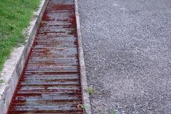 Wässern Sie Abfluss- oder Abzugsgrabenmetallgitter auf der Straße Stockfotos