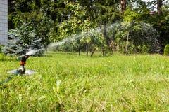 Wässern Sie Berieselungsanlage in der Aktion und den Rasen wässern lizenzfreie stockbilder