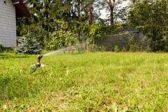Wässern Sie Berieselungsanlage in der Aktion und den Rasen wässern stockbild