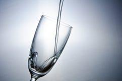 Wässern Sie das Fallen in Glas Lizenzfreie Stockfotografie
