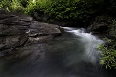 Wässern Sie das Fließen über die großen Felsen in Wasserfallwald Lizenzfreie Stockfotos