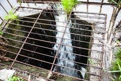 Wässern Sie das Fließen in den Abflusskanal auf der Verdammung Lizenzfreie Stockfotos