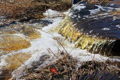 Wässern Sie das Fließen in den Abzugsgraben während des Frühlinges Lizenzfreie Stockfotografie