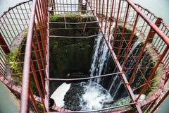 Wässern Sie das Fließen in den runden Abflusskanal auf der Verdammung Lizenzfreie Stockfotografie