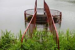 Wässern Sie das Fließen in den runden Abflusskanal auf der Verdammung Stockfotos