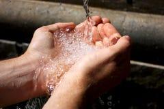Wässern Sie das Fließen in die Hände des Mannes Stockbilder
