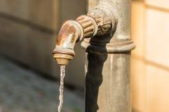 Wässern Sie das Fließen vom Rohr auf der Straße in Lindau Lizenzfreies Stockfoto