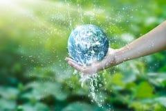 Wässern Sie das Gießen auf die Planetenerde, die auf menschliche Hand gesetzt wird lizenzfreie stockfotos