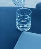 Wässern Sie das Gießen in ein Glas und in einen Laptop lizenzfreie stockbilder