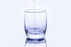 Wässern Sie das Gießen in Glas Stockbild