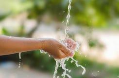 Wässern Sie das Gießen in Kinderhand auf Naturhintergrund, Umwelt issu Lizenzfreie Stockbilder