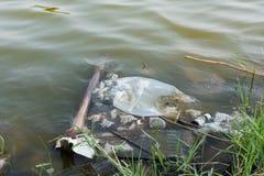 Wässern Sie, das mit verschiedenem Abfall verunreinigt wird Lizenzfreies Stockfoto