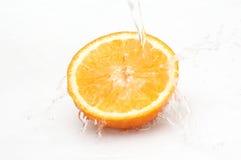 Wässern Sie das Spritzen auf Hälfte der reifen, saftigen Orange. stockbilder