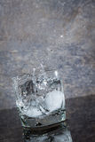 Wässern Sie das Spritzen vom Glas auf einer nassen Oberfläche lizenzfreie stockbilder