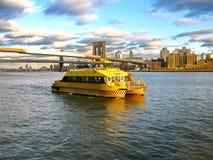 Wässern Sie das Taxi und Brooklyn-Brücke, gesehen von Pier 17, an den niedrigeren Mann-Stunden Lizenzfreie Stockfotos