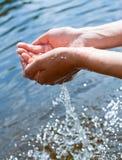 Wässern Sie in den Händen Lizenzfreie Stockbilder