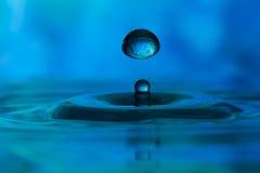 Wässern Sie den Tropfen, der der Bewegung gestoppt wird, bevor Sie in einem Wasserbecken spritzen Lizenzfreies Stockfoto