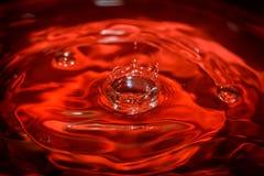 Wässern Sie den Tropfen Wellen mit rotem Hintergrund und Reflexion Lizenzfreies Stockfoto