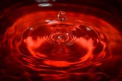 Wässern Sie den Tropfen Wellen mit rotem Hintergrund und Reflexion Lizenzfreie Stockfotos
