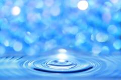 Wässern Sie die blaue Flüssigkeit, die durch eine Kreiswelle auf einem hellen bokeh b gekreuzt wird stockbilder